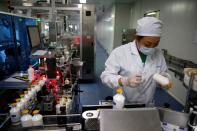 An employee works at a packaging line for chicken vaccine at Ringpu Biotech in Tianjin