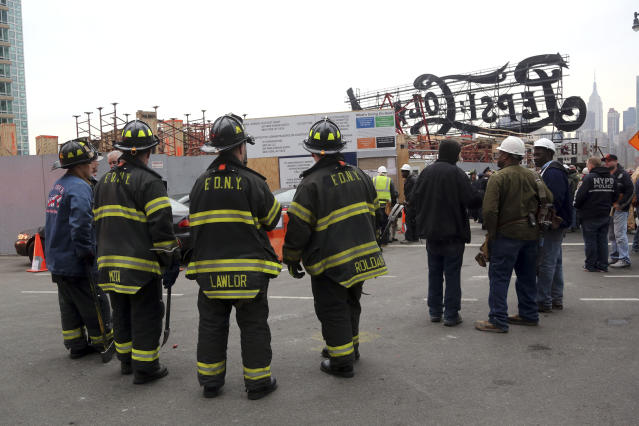 """Firefighters, police officers and construction workers work the scene of a crane collapse at a construction site in the Queens borough of New York, Wednesday, Jan. 9, 2013, behind a big neon """"Pepsi Cola"""" sign, a local landmark. The Fire Department of New York says the 200-foot crane collapsed onto a building under construction, injuring seven people, three of them seriously. (AP Photo/Mary Altaffer)"""