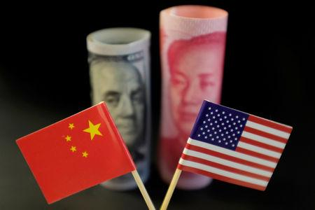U.S. and Chinese flags are seen in front of a U.S. dollar banknote featuring American founding father Benjamin Franklin and a China's yuan banknote featuring late Chinese chairman Mao Zedong in this illustration picture taken May 20, 2019. Picture taken May 20, 2019. REUTERS/Jason Lee/Illustration