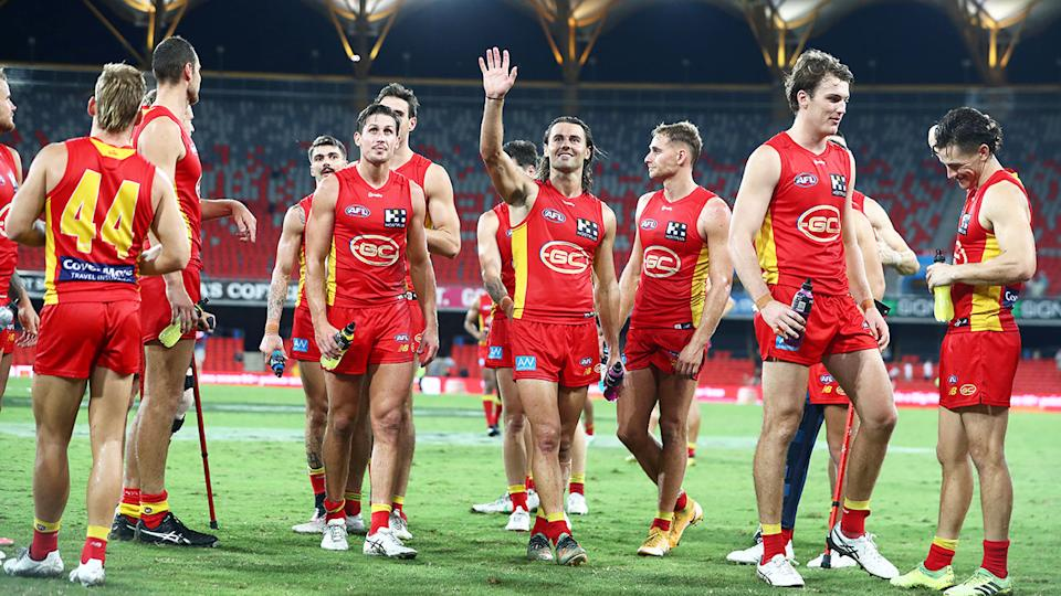 Seen here, Gold Coast Suns players walk off after their round two win in the AFL.