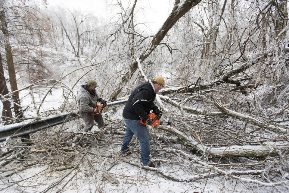 Area residents work to clear downed trees along Honeysuckle Lane on Feb. 16, 2021, in Huntington, W.Va., (Sholten Singer / The Herald-Dispatch via AP file)