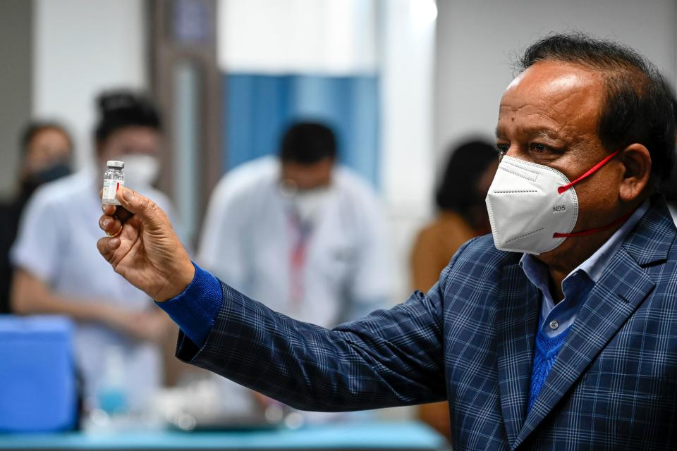 India's Health Minister Harsh Vardhan displays a vial of a Covid-19 coronavirus vaccine at the All India Institute of Medical Science (AIIMS) in New Delhi on January 16, 2021. (Photo by Sajjad HUSSAIN / AFP) (Photo by SAJJAD HUSSAIN/AFP via Getty Images)