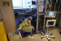 Jodie Ford, an ICU nurse, moves electrical cords for medical machines, outside the room of a patient suffering from COVID-19, in an intensive care unit at the Willis-Knighton Medical Center in Shreveport, La., Tuesday, Aug. 17, 2021. (AP Photo/Gerald Herbert)