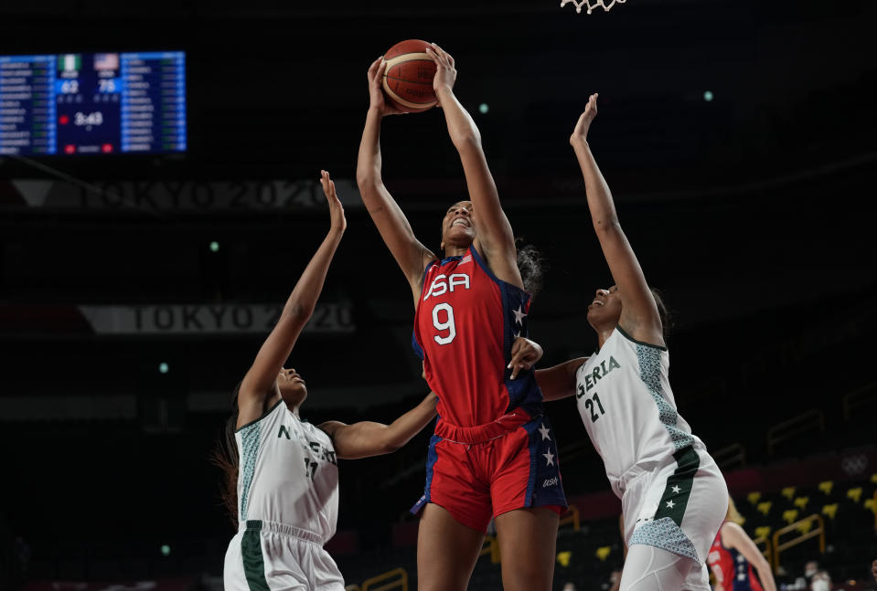United States' A'Ja Wilson (9), center, grabs a rebound between Nigeria's Adaora Elonu (11), left, and Atonye Nyingifa (21) during women's basketball preliminary round game at the 2020 Summer Olympics, Tuesday, July 27, 2021, in Saitama, Japan. (AP Photo/Eric Gay)