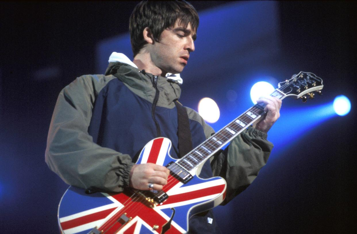 UNITED KINGDOM - APRIL 01:  Photo of Noel GALLAGHER and BRITPOP and OASIS; Noel Gallagher performing live onstage, playing Epiphone Sheraton Union Jack guitar at Maine Road, Britpop  (Photo by Patrick Ford/Redferns)