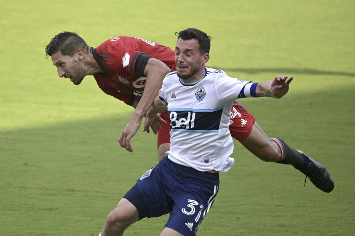 Vancouver Whitecaps midfielder Russell Teibert (31) and Toronto FC defender Omar Gonzalez (44) collide while competing for a ball during the second half of an MLS soccer match, Saturday, April 24, 2021, in Orlando, Fla. Gonzalez received a yellow card on the play. (AP Photo/Phelan M. Ebenhack)