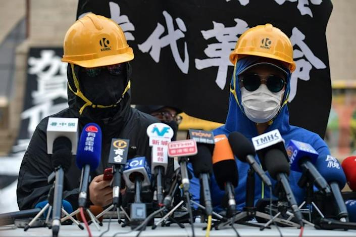 A group of protesters, their faces obscured by masks and yellow hard hats, held an impromptu press conference in a Hong Kong park and called on people to hit the streets on Tuesday (AFP Photo/Nicolas ASFOURI)