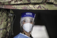 Army medical personnel, wearing a protective suit, works at a quick coronavirus testing area which was set up to ease the pressure on hospital emergency wards, following the surge of COVID-19 case numbers, in Milan, Italy, Friday, Nov. 13, 2020The central government has put under partial lockdown some regions where the rate of virus transmission is particularly high and hospitals are running out of staff or space for patients, including in Lombardy, the northern region where the pandemic first erupted in Italy in February. (AP Photo/Luca Bruno)