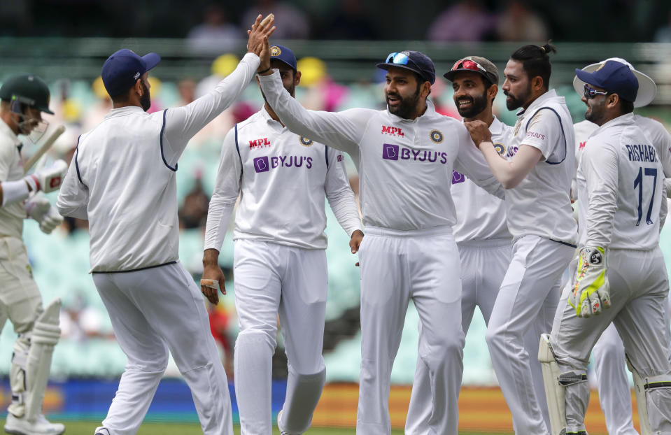 Indian players celebrate the dismissal of Australia's David Warner, left, during play on day one of the third cricket test between India and Australia at the Sydney Cricket Ground, Sydney, Australia, Thursday, Jan. 7, 2021. (AP Photo/Rick Rycroft)