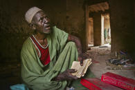 In this photo taken Tuesday, Mar. 16, 2004, Alfa Telfi, 72, reads from his crumbling ancient Islamic manuscripts in his mud-walled house in Timbuktu, Mali. Islamist extremists torched a library containing historic manuscripts in Timbuktu, the mayor of the town said Monday, Jan. 28, 2013, while owners have succeeded in removing some of the manuscripts from Timbuktu to save them and others have been carefully hidden away from the Islamists. (AP Photo/Ben Curtis)