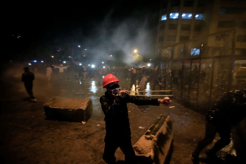 A demonstrator uses a slingshot to throw a stone during a protest against the newly formed government near the government headquarters in downtown Beirut