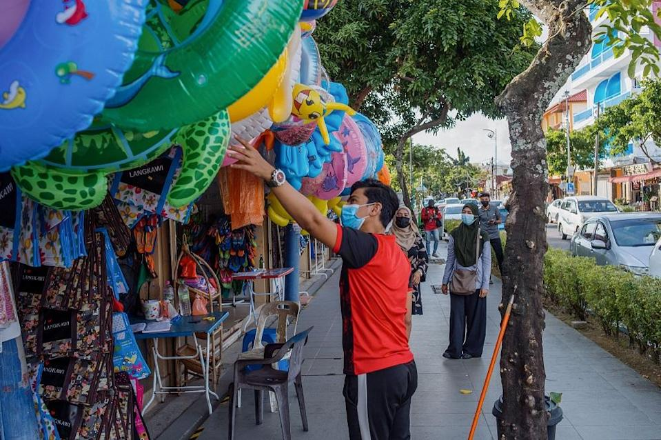 A vendor is seen serving a customer at one of the shops along Pantai Cenang in Langkawi.
