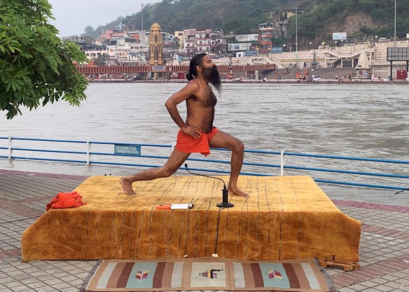 India's yoga guru Baba Ramdev performing yoga on the banks of the river Ganges ahead of International Yoga day, in the northern town of Haridwar, India, on 19 June: REUTERS