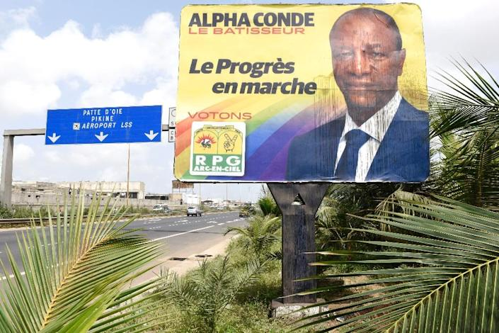 A vandalized billboard showing Alpha Conde, on the side of a highway in Dakar, on October 9, 2015 (AFP Photo/Seyllou Diallo)