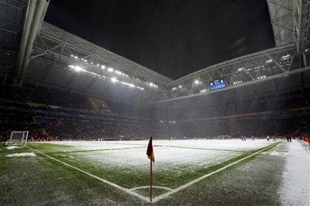 Workers clean the snow from the pitch after the Champions League soccer match between Galatasaray and Juventus was paused for 20 minutes due heavy snowfall in Istanbul December 10, 2013. REUTERS/Murad Sezer