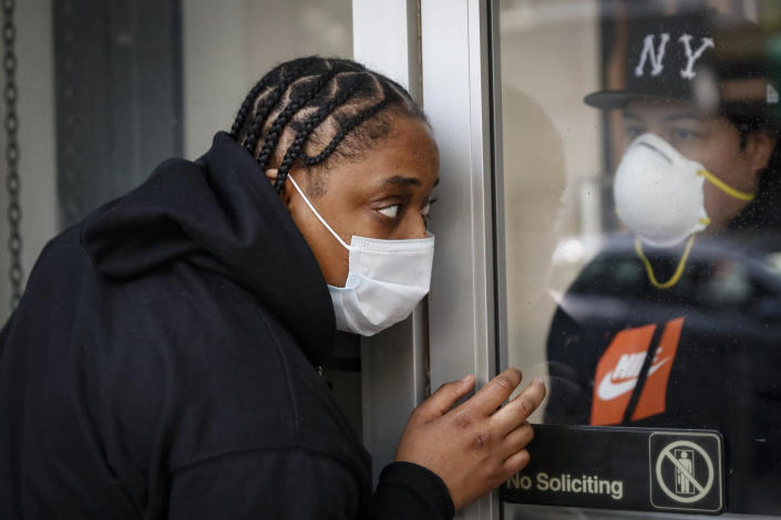 Roni Colvert attempts to make purchases from curb-side at The Loop fashion and shoe store as businesses slowly begin to reopen after social distancing restrictions shuttered storefronts nationwide, Tuesday, May 26, 2020, in Yonkers, N.Y. (AP Photo/John Minchillo)