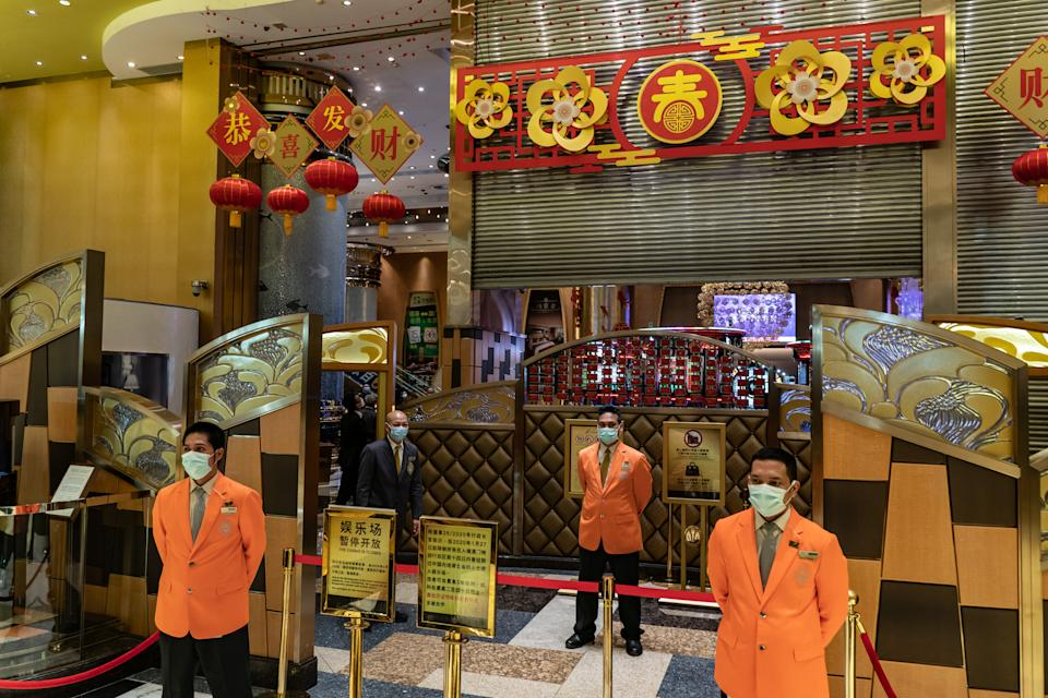 MACAU, CHINA - FEBRUARY 04: Employees wearing protective masks stand at the entrance of a gambling hall as they shut a gate at the Grand Lisboa Hotel on February 4, 2020 in Macau, China. Macau government announced to close casinos for two weeks after a hotel worker is infected. Macau has 10 confirmed cases of Novel coronavirus (2019-nCoV), with over 20,000 confirmed cases around the world, the virus has so far claimed over 400 lives.(Photo by Anthony Kwan/Getty Images)