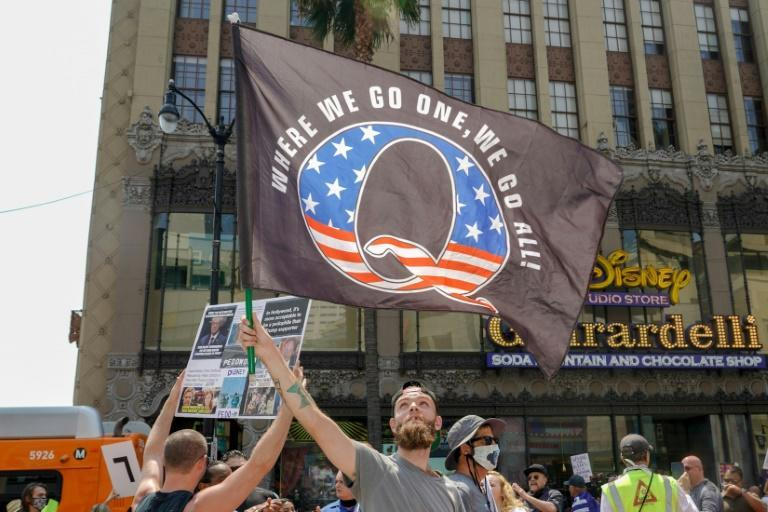 This file photo taken on August 22, 2020 shows demonstrators from conspiracy theorist group QAnon , as group which claims without evidence, that the pandemic is a conspiracy by a cabal of satanist paedophiles who control the world