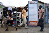 Liberians walk past an Ebola information and sanitation station in Monrovia on September 30, 2014 (AFP Photo/Pascal Guyot)