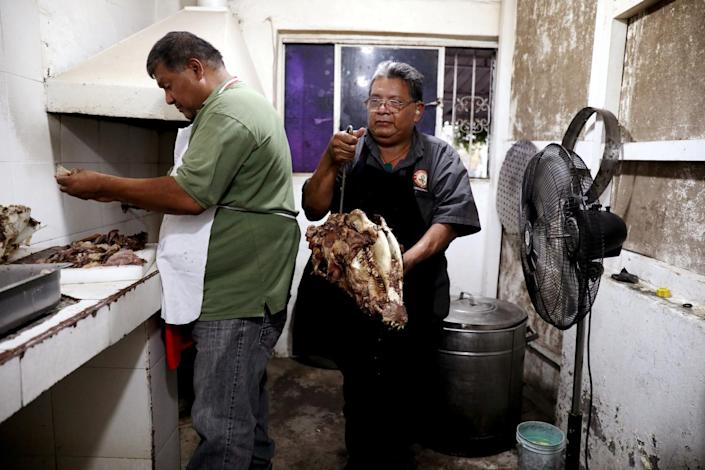 Rosendo Godinez, left, and his brother Cesar Godinez, remove the meat from cooked cows heads.