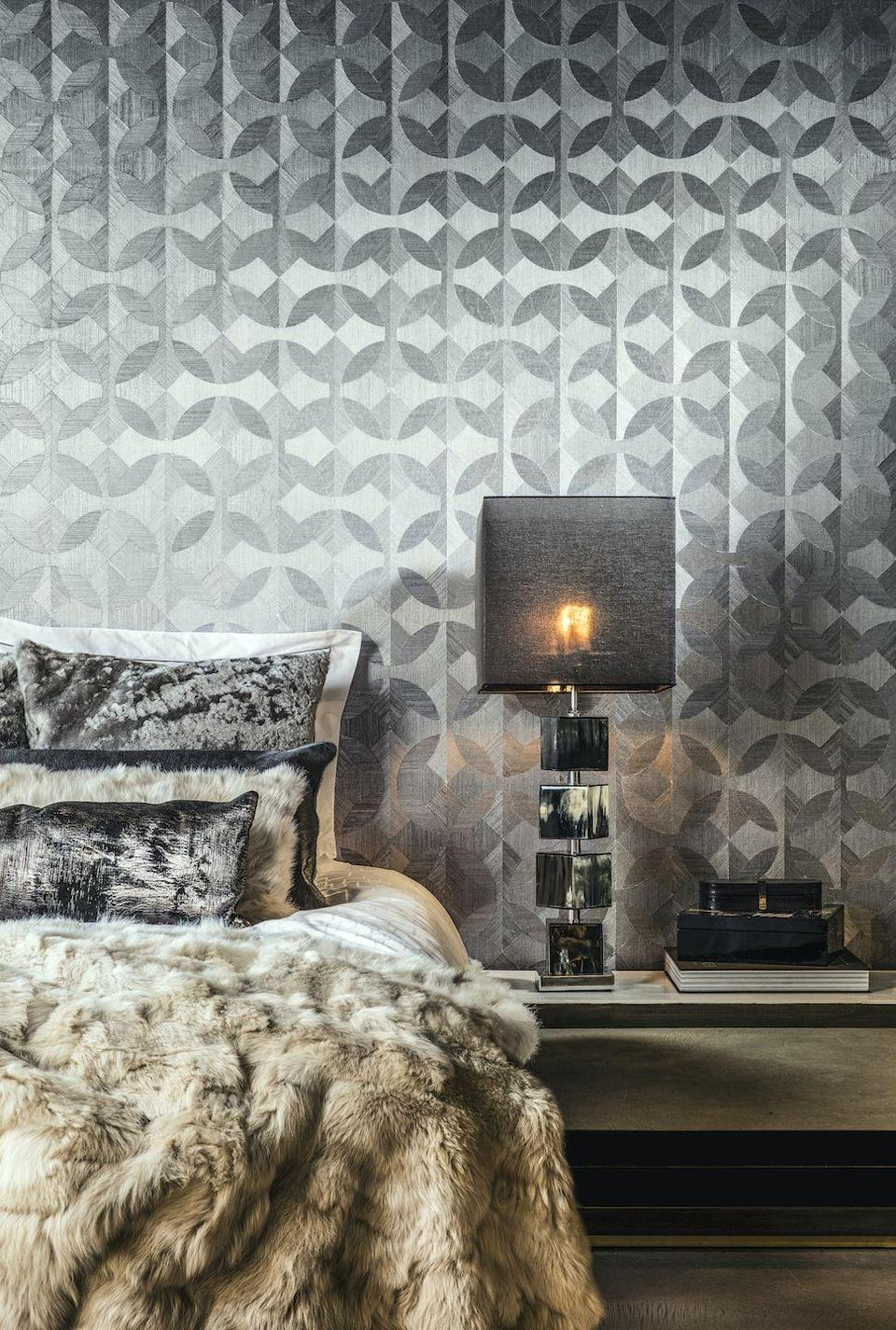 """<p>Wallpaper is a great way to add grey to a bedroom, and there are some fantastic designs around. The contrasting lines and colour variations in this geo pattern give an extra dimension to the design, making it look like an optical illusion. It also has a subtle shine which reflects the light. It makes a great backdrop to the bed, and the fur throw and cushions look SO luxurious.</p><p>Pictured: <a href=""""https://www.arte-international.com/en/collections/oculaire/unite"""" rel=""""nofollow noopener"""" target=""""_blank"""" data-ylk=""""slk:Unite 80602 Oculaire wallcovering, Arte"""" class=""""link rapid-noclick-resp"""">Unite 80602 Oculaire wallcovering, Arte</a></p>"""