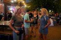 Few masks are seen as people drink and eat at the Truck Yard beergarden in Houston, Texas, on April 9, 2021 -- a glimpse, optimists say, at a 'post-pandemic' world