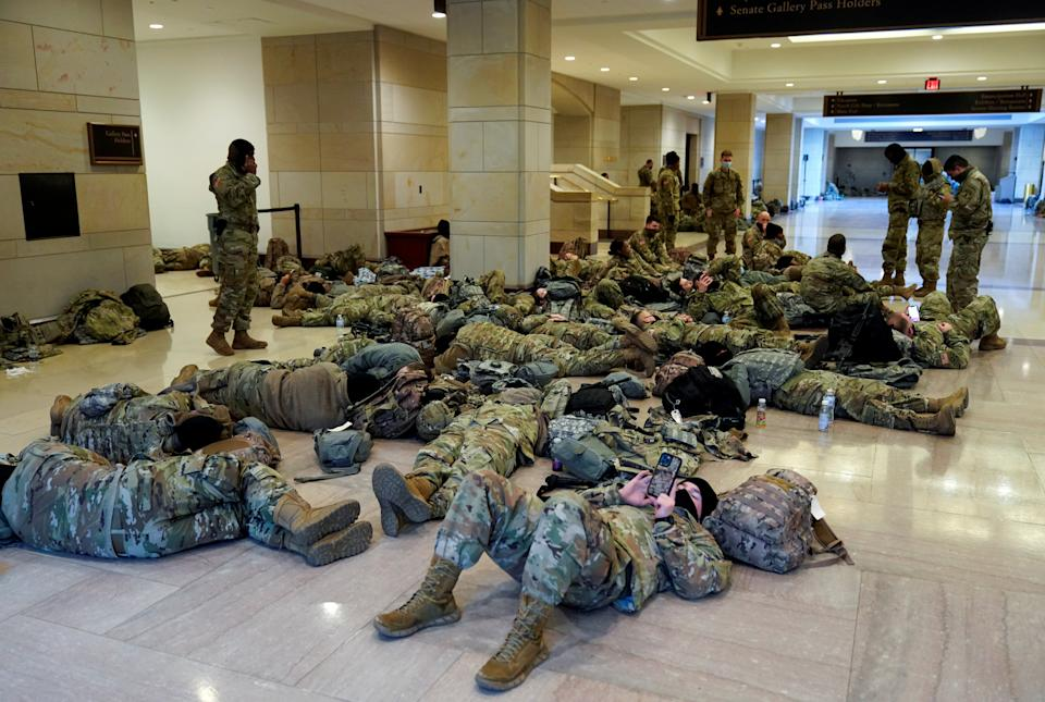 National Guard members sleep in the Capitol Visitor Centre before Democrats begin debating one article of impeachment against Donald Trump (REUTERS)
