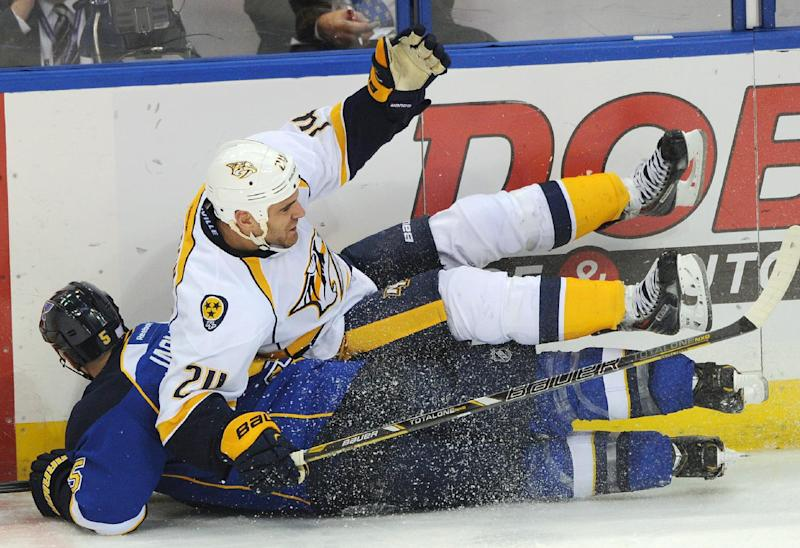 St. Louis Blues' Barret Jackman (5) slides under Nashville Predators' Eric Nystrom (24) during the second period of an NHL hockey game Thursday, Oct. 3, 2013, in St. Louis. (AP Photo/Bill Boyce)