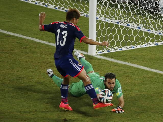Japan's Yoshito Okubo (L) tries to steal the ball away from Greece's Orestis Karnezis during their 2014 World Cup Group C soccer match at the Dunas arena in Natal June 19, 2014. REUTERS/Carlos Barria (BRAZIL - Tags: SOCCER SPORT WORLD CUP)