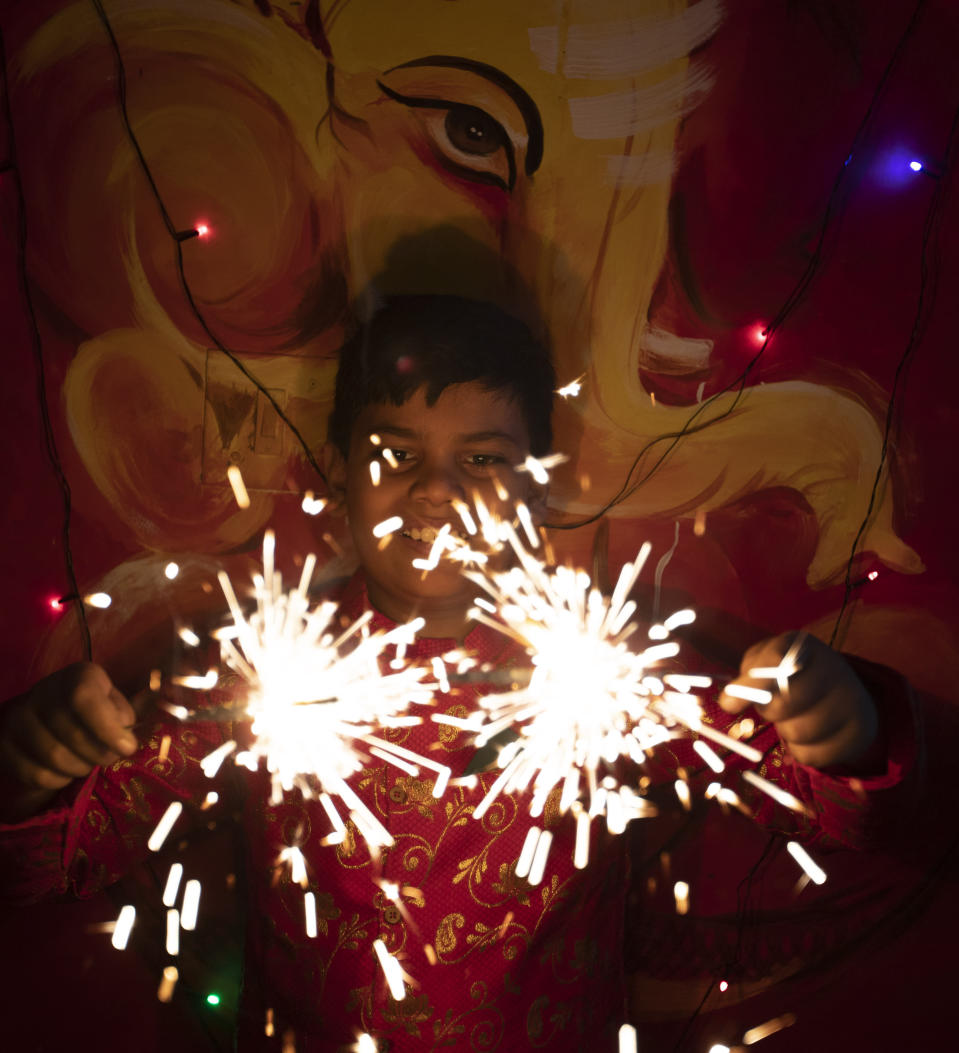 A child plays with fireworks during Diwali, the Hindu festival of lights, in Prayagraj, India, Saturday, Nov. 14, 2020. Hindus across the country are celebrating Diwali where people decorate their homes with lights and burst fireworks. (AP Photo/Rajesh Kumar Singh)