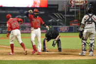 Los Angeles Angels' Brian Goodwin, second from left, is congratulated by David Fletcher, left, as Houston Astros catcher Martin Maldonado, right, stands by and home plate umpire Cory Blaser wipes the plate after Goodwin hit a two-run home run during the fourth inning of a baseball game Friday, July 31, 2020, in Anaheim, Calif. (AP Photo/Mark J. Terrill)