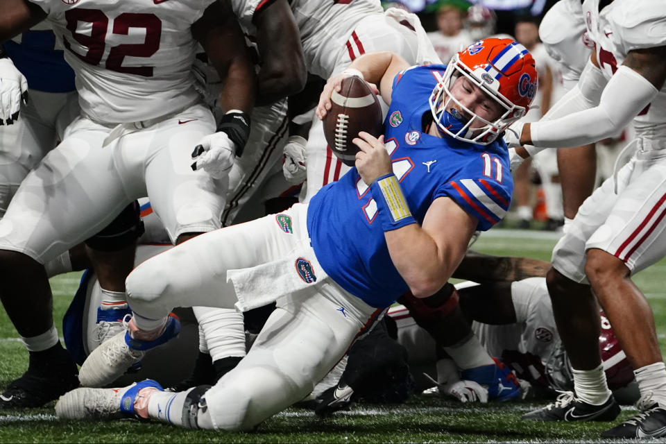 Florida quarterback Kyle Trask (11) leaps into the end zone for a touchdown against Alabama during the first half of the Southeastern Conference championship NCAA college football game, Saturday, Dec. 19, 2020, in Atlanta. (AP Photo/Brynn Anderson)