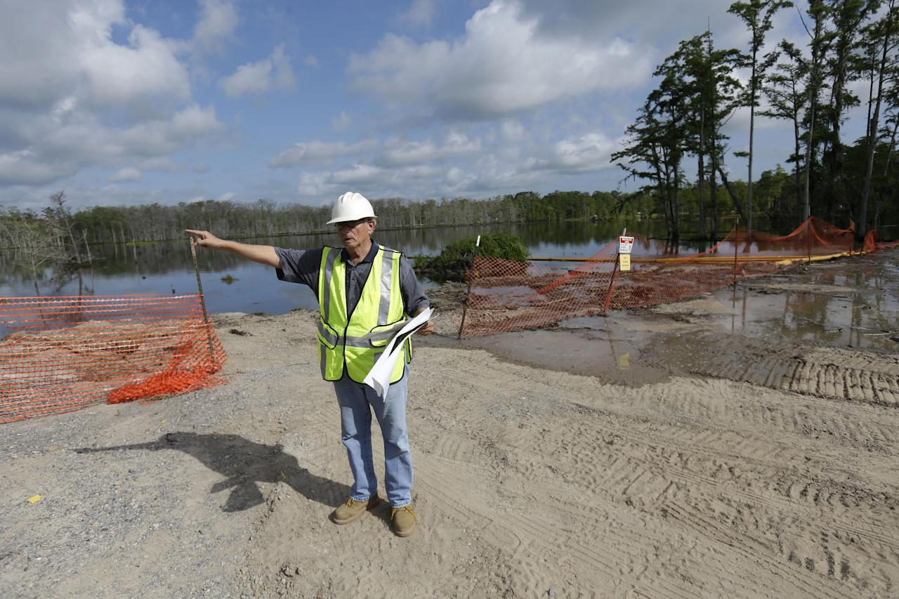 In this Thursday, June 27, 2013 photo, Texas Brine, Inc. spokesperson Sonny Cranch highlights work being done to remediate the approximately 22-acre sinkhole, seen behind him, in Bayou Corne, La. Neighbors in tiny Bayou Corne face a wrenching decision after a huge sinkhole opened up near their community: Do they stay put or should they pack up and move? The sinkhole resulted from a collapsed underground salt dome cavern about 40 miles south of Baton Rouge. After oil and natural gas came oozing up and acres of swampland liquefied into muck, the community's 350 residents were advised to evacuate. Texas Brine Co., the operator of the salt dome, is negotiating buyouts of residents who have not joined lawsuits against the company. (AP Photo/Gerald Herbert)
