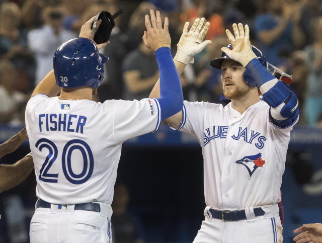 Toronto Blue Jays' Brandon Drury, right, is met by teammate Derek Fisher at home plate after hitting a grand slam during fourth-inning baseball game action against the Texas Rangers in Toronto, Monday, Aug. 12, 2019. (Fred Thornhill/The Canadian Press via AP)