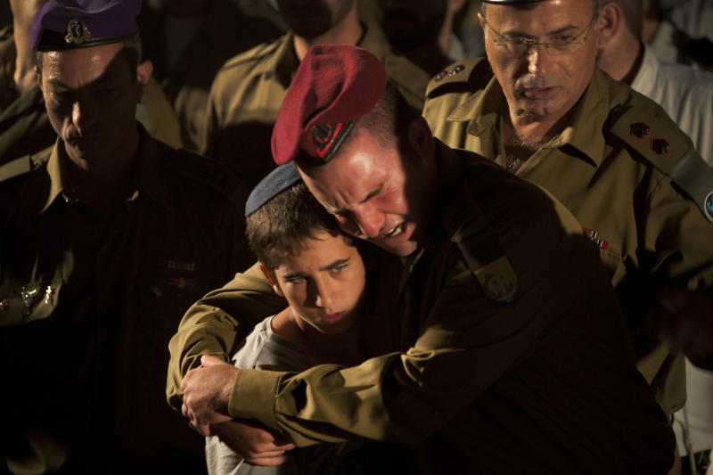 Israeli soldiers and relatives react during the funeral of Cpl. Netanel Yahalomi, 20, in the Israeli city of Modiin, early Sunday, Sept. 23, 2012. Yahalomi was killed Friday in a shootout between  Islamic militants and Israeli troops along Israel's southern border with Egypt. The Israeli troops returned fire, killing the militants. (AP Photo/Oded Balilty)