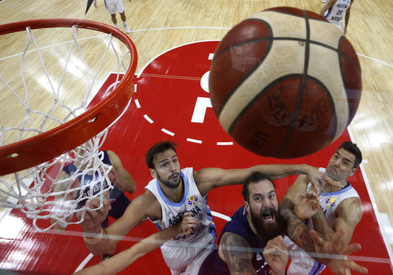 Serbia's Miroslav Raduljica in action with Argentina's Marcos Delia and Luis Scola during the FIBA Basketball World Cup quarter final match between Serbia and Argentina, in Dongguan, China, Tuesday, Sept. 10, 2019. (Kim Kyung-Hoon/Pool Photo via AP)