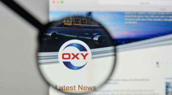 A magnifying glass zooms in on the Occidental Petroleum (OXY) website.
