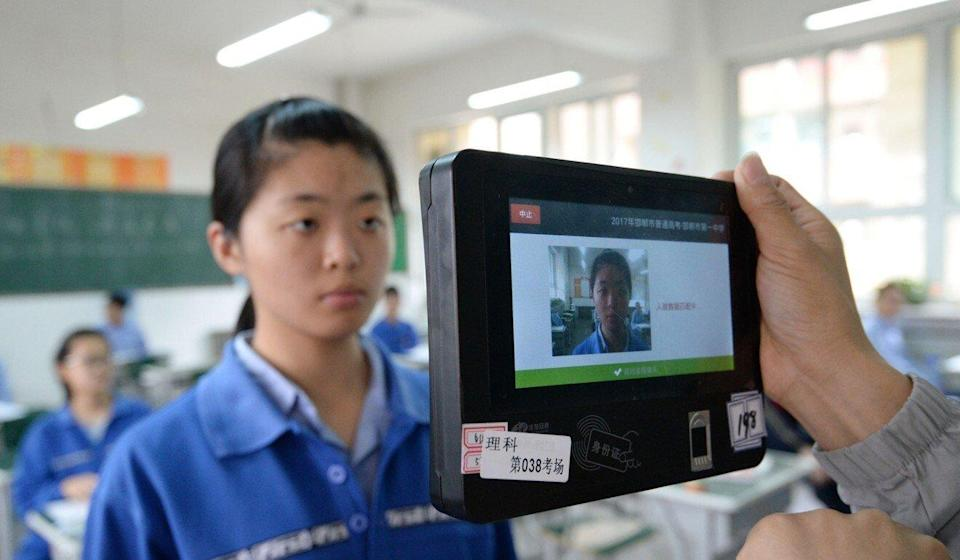 A teacher uses a machine which employs both fingerprint and facial recognition technology to check the identification of a student before a simulated college entrance exam in Handan in China's northern Hebei province on June 6, 2017. Photo: STR/AFP via Getty