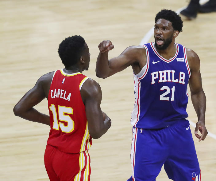 Philadelphia 76ers center Joel Embiid, right, makes a point to Atlanta Hawks center Clint Capela during the first half of Game 5 of an NBA basketball Eastern Conference semifinal Wednesday, June 16, 2021, in Philadelphia. (Curtis Compton/Atlanta Journal-Constitution via AP)