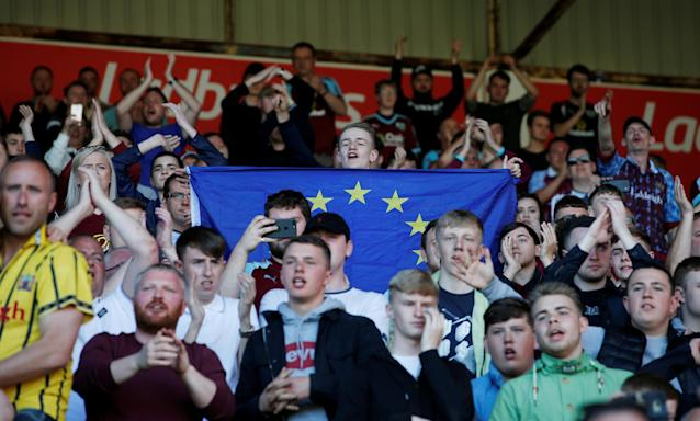 "Soccer Football - Premier League - Burnley vs AFC Bournemouth - Turf Moor, Burnley, Britain - May 13, 2018 Burnley fans with a European flag after the match Action Images via Reuters/Craig Brough EDITORIAL USE ONLY. No use with unauthorized audio, video, data, fixture lists, club/league logos or ""live"" services. Online in-match use limited to 75 images, no video emulation. No use in betting, games or single club/league/player publications. Please contact your account representative for further details."