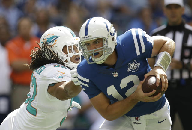 Indianapolis Colts' Andrew Luck (12) is chased by Miami Dolphins' Philip Wheeler (52) during the first half an NFL football game Sunday, Sept. 15, 2013, in Indianapolis. (AP Photo/AJ Mast)
