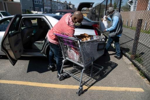 Anthony Lorenzo Green (R) and Bernard Stevenson load groceries into a car for delivery to the needy