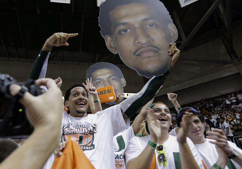 Miami's Julian Gamble, left, holds up a cardboard cut-out figure of himself as he celebrates with students after the second half of a NCAA college basketball game in Coral Gables, Fla., Saturday, March 9, 2013. Down to its third try and last chance, Miami came through. Kenny Kadji scored a season-high 23 points to help the sixth-ranked Hurricanes win the Atlantic Coast Conference championship outright by beating Clemson 62-49 on Saturday. (AP Photo/J Pat Carter)