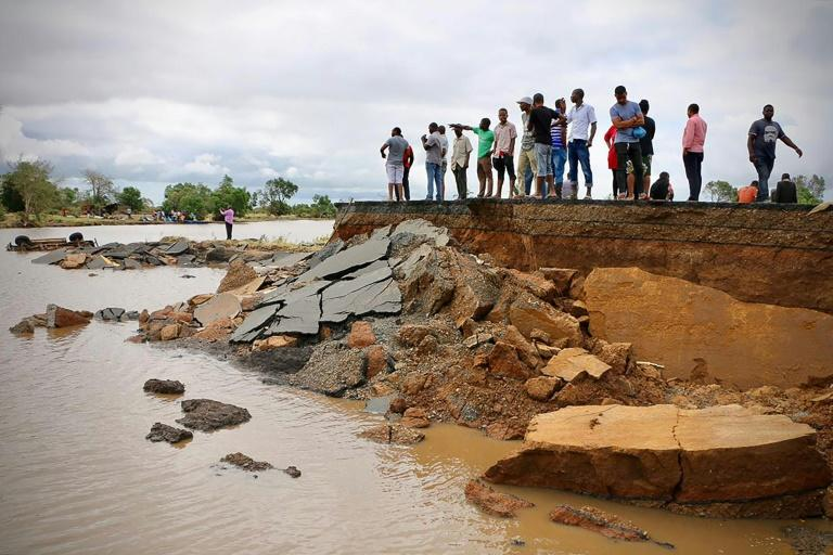 People stand beside a damaged section of the road between Beira and Chimoio in Nhamatanda district, central Mozambique