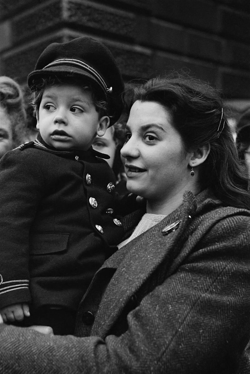 A woman holds up a toddler to watch the royal procession in London for the wedding.