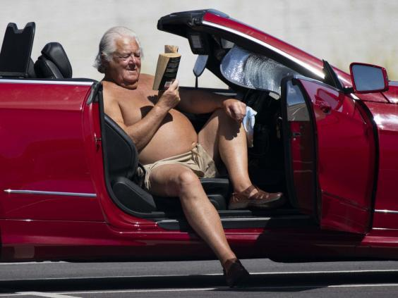 A man reads a book while sitting in the driver seat of his car in the sun in the car park of a Trago Mills department store in Merthyr Tydfil, United Kingdom (Getty Images)