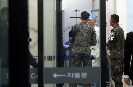 A South Korean soldier talks with a surgeon at a hospital where a North Korean soldier who defected to the South after being shot and wounded by the North Korean military is hospitalized, in Suwon