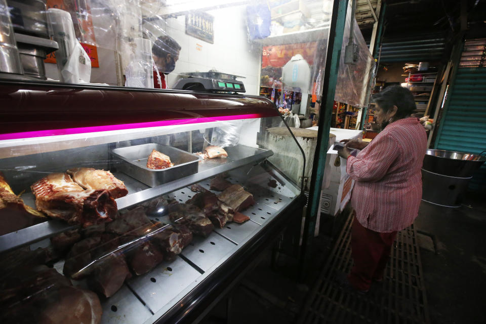 Josefina Rodriguez uses coupons provided by the municipality of Iztapalapa to buy meat at a corner shop in Iztapalapa, Mexico City, Thursday, Oct. 8, 2020. The municipal government of Iztapalapa is providing coupons to help poor families cope with the hardship created by the new coronavirus pandemic economic slowdown. (AP Photo/Marco Ugarte)