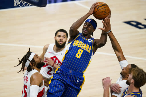 Indiana Pacers guard Justin Holiday (8) shoots over Toronto Raptors forward DeAndre' Bembry (95) during the first half of an NBA basketball game in Indianapolis, Sunday, Jan. 24, 2021. (AP Photo/Michael Conroy)