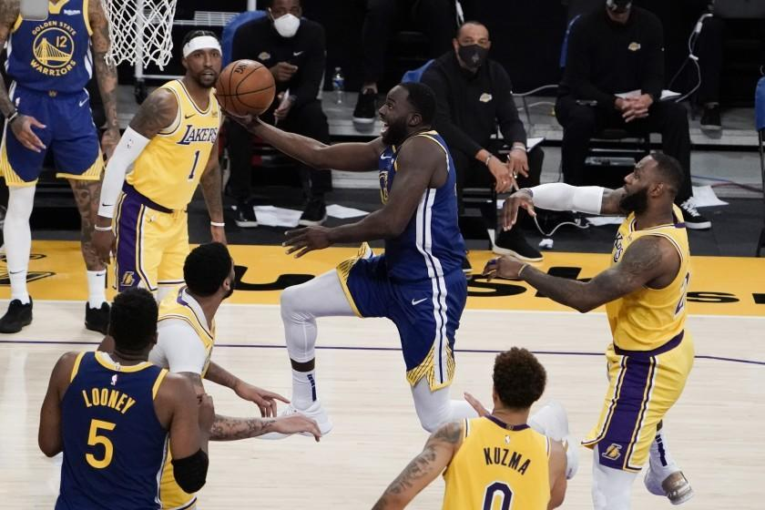 Golden State Warriors' Draymond Green, center, drives to the basket past Los Angeles Lakers' LeBron James, right, during the second half of an NBA basketball game, Monday, Jan. 18, 2021, in Los Angeles. The Warriors won 115-113. (AP Photo/Jae C. Hong)